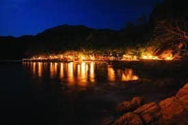 A view of a torchllit island at night