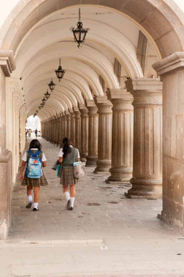 School kids walking through some of the many Colonial arches in Antigua