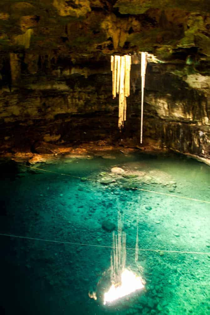 Sun lighting up the green water in the underground Zaci cenote in Valladolid Yucatan