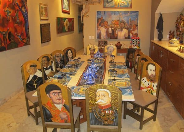 Dining table and chairs decorated in colorful Mexican artwork at La Casa de los , Valladolid, Yucatan