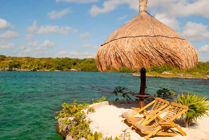 A palapa at the edge of clear turquoise water with two lounge chairs for relaxing. One of the things to do in our Xel Ha review.