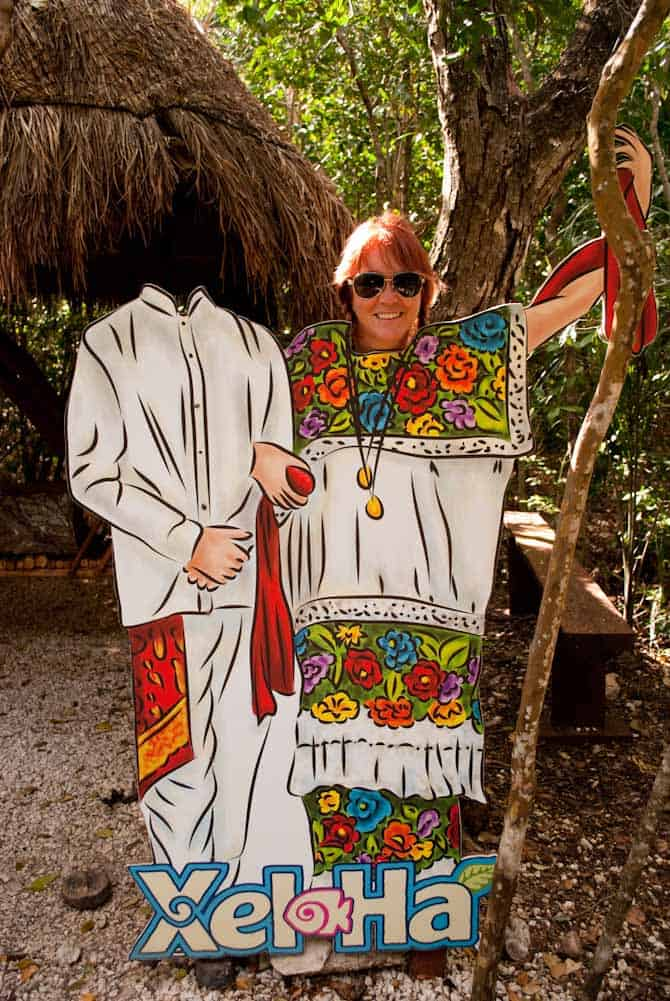Sarah's head on top of a wooden cut out of a lady in a colorful traditional Mexican dress. One of the things in our Xel Ha review and things to do.