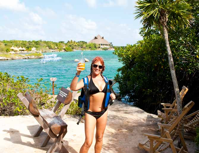 Sarah in a black bikini and life vest holding a rum and pina at Xel Ha eco Park, Riviera Maya