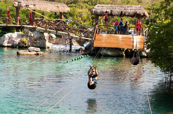 Nathan flying above the water on a Xel Ha zipline near Cancun Mexico