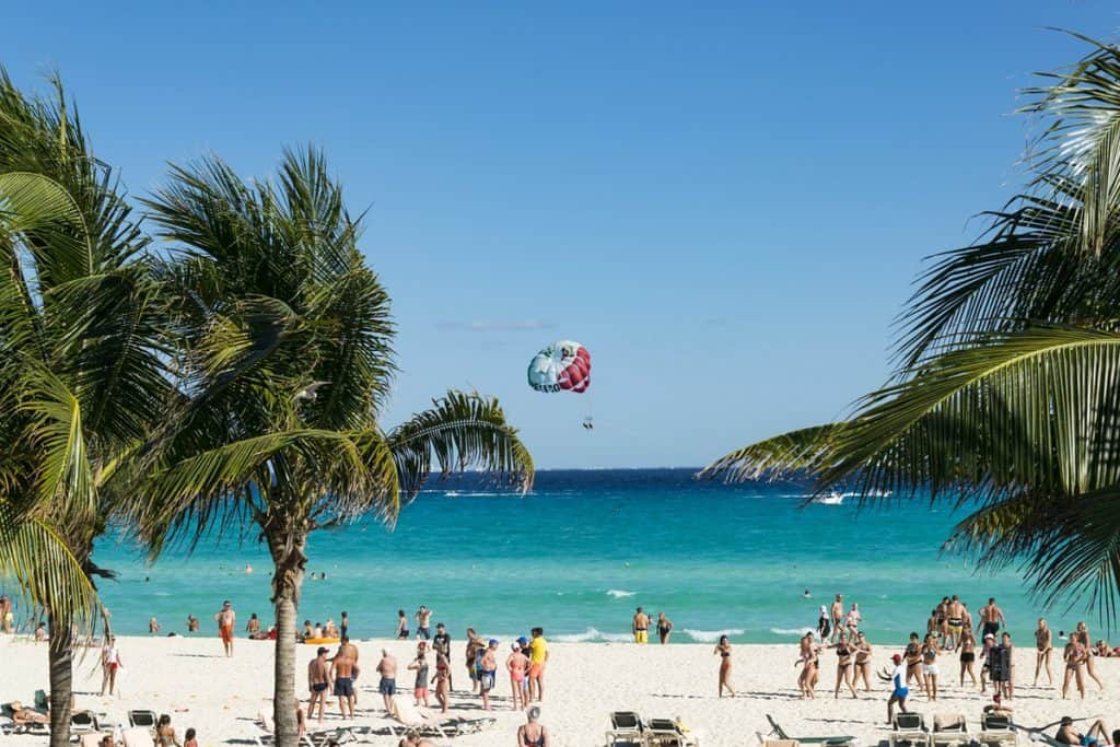 Beach with white sand, turquoise water, palm trees, people on beach, parasailer in the sky