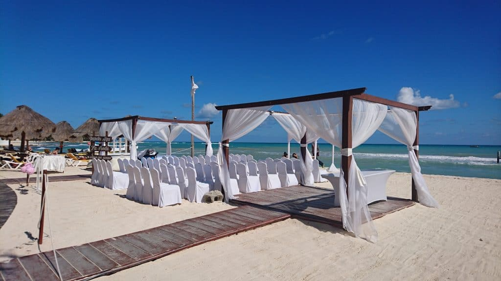 Beach wedding set up with white chairs, Flowing white fabric and palapas