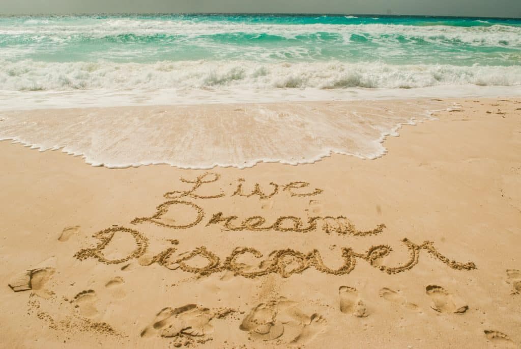 Live Dream Discover written in the sand