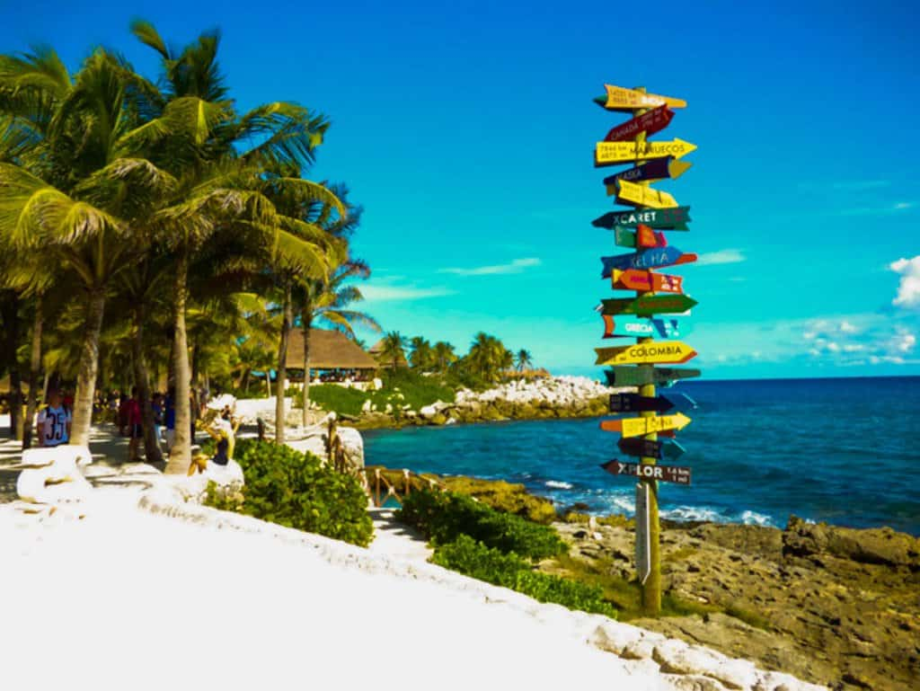 Sign post, palm trees and ocean at Xcaret