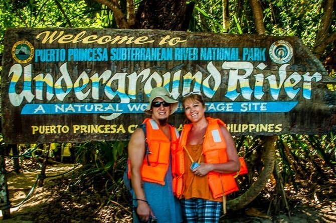 Sarah and Nathan standing in front of a big sign saying: Welcome to Puerto Princesa Underground River. It is one of the top things to do in Palawan