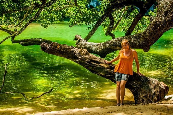 Sarah leaning against a tree whose branches are overhanging a bright green river in Puerto Princesa, Palawan.