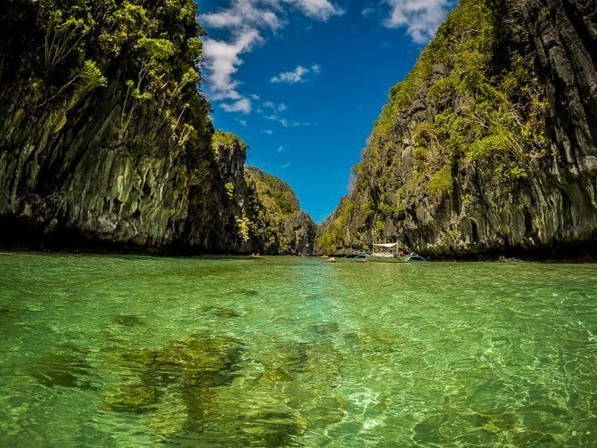 A small tour boat floating between two rocky cliffs near El Nido Palawan Island Philippines