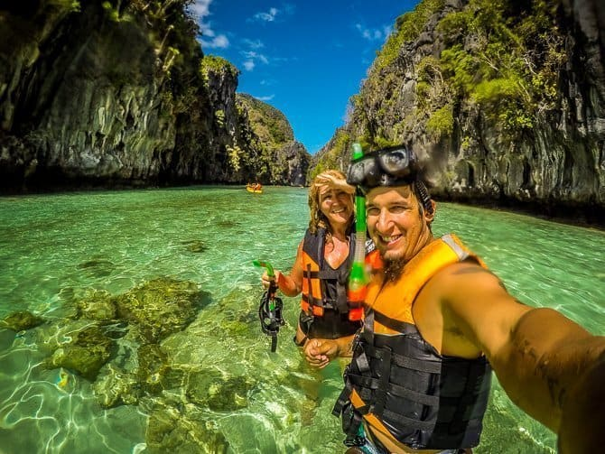 Nathan and Sarah in snorkel gear standing waist deep in the crystal clear waters near El Nido