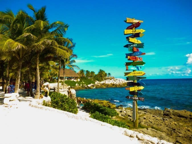 Sign post on the beach at Xcaret Park with multiple colorful arrows pointing directions to Xcaret activities.