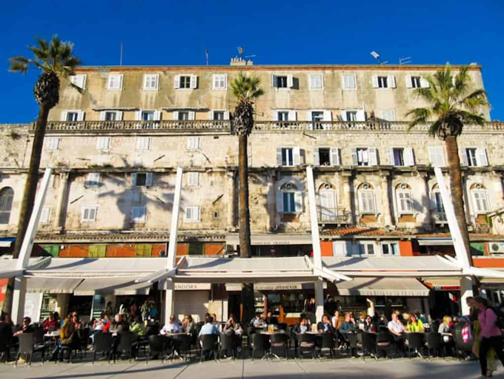 Looking at a group of restaurants on the Riva in Split with outdoor seating and umbrellas. Split vs Dubrovnik, Croatia