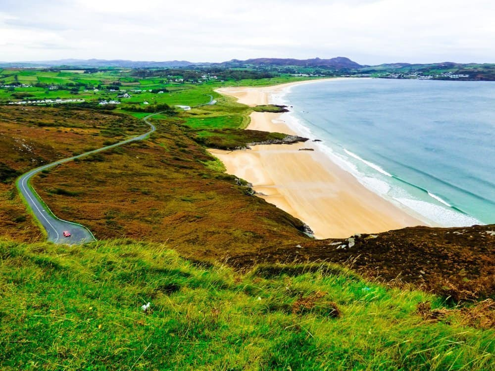 A view of green hills and fields beside the beach on a Northern Ireland Road trip