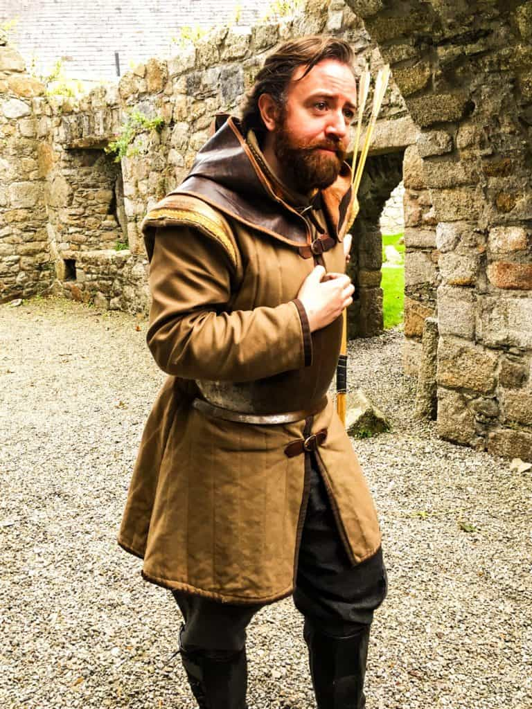 An actor dressed in a Medieval leather tunic holding arrows as he describes life at Dalkey Castle hundreds of years ago