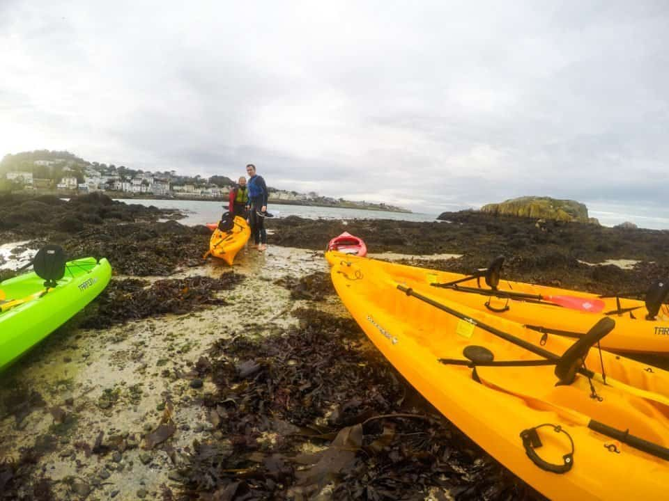 A green kayak and two yellow kayaks pulled up on the rocky shore of Dalkey Island