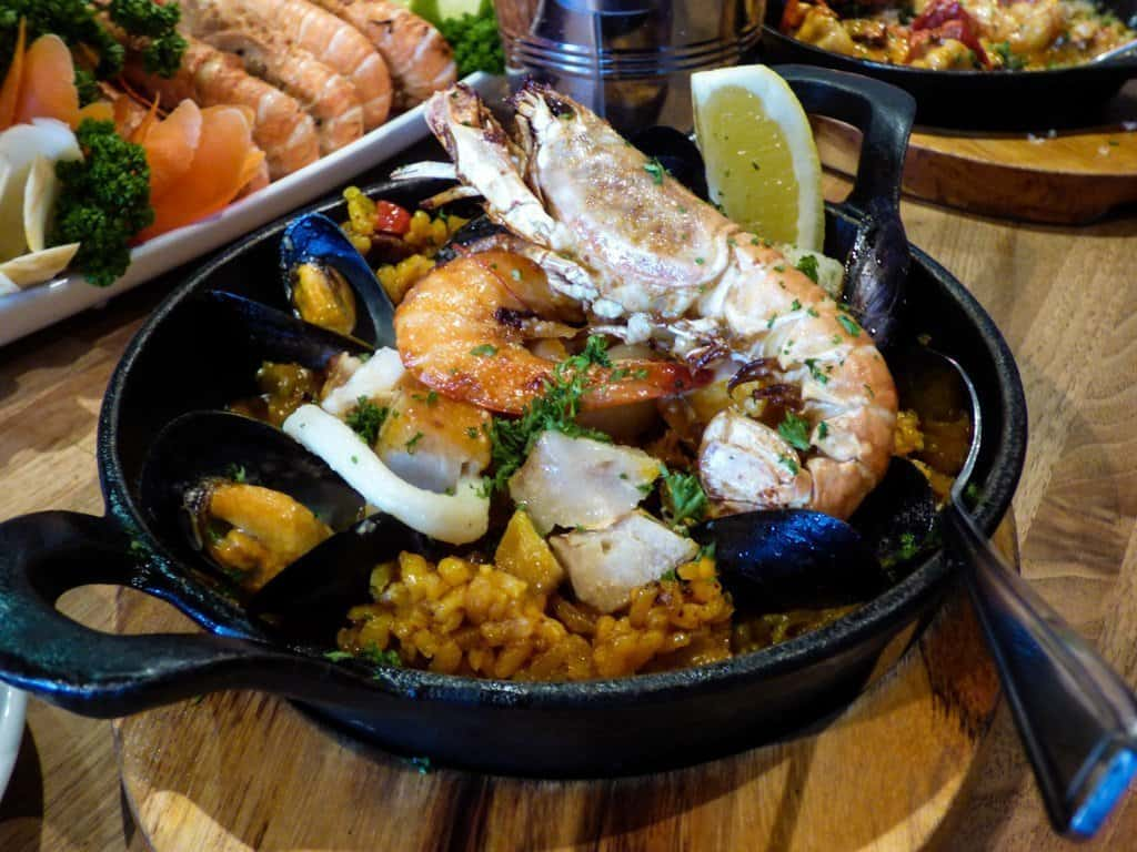 A dish of seafood Paella with a giant crab leg on the top
