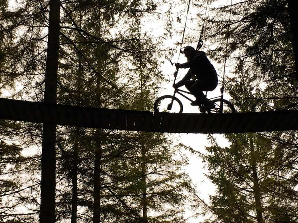 Looking up into the trees as Nathan attempts to ride a bike across a narrow hanging bridge at Zipit Adventure Park