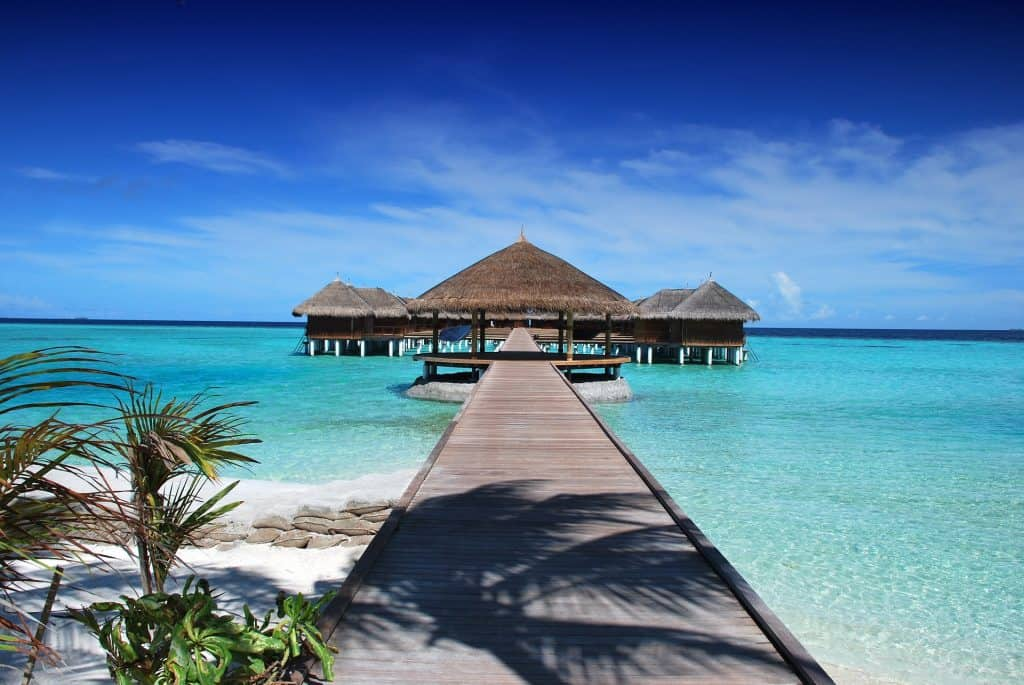 Cabana sitting over crystal clear blue water and white sand beach in the Maldives