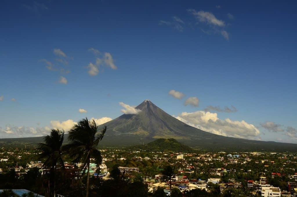 Mayon Volcano rising up behind the city