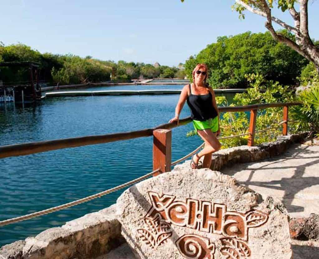 Sarah standing behind a rock Xel Ha sign at the water park in Riviera Maya Mexico