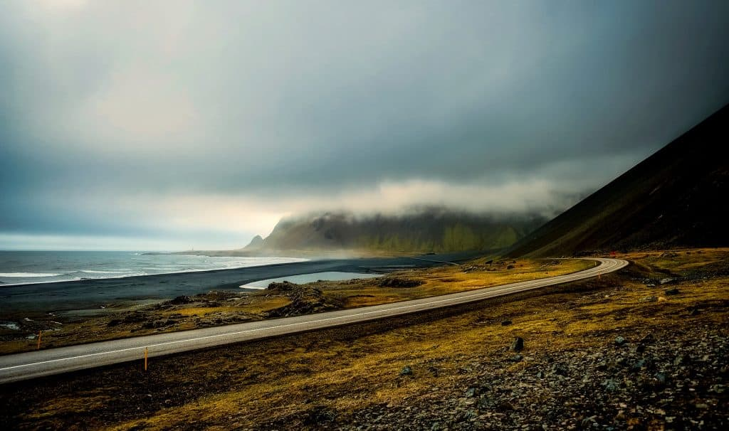 A coastal road with mountains in the background with low clouds