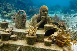 Statue of a person at a table at the Cancun Underwater Museum
