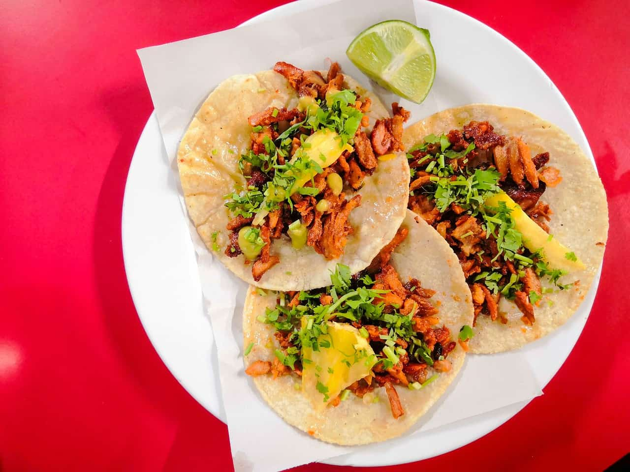 3 tacos al pastor on a red plate