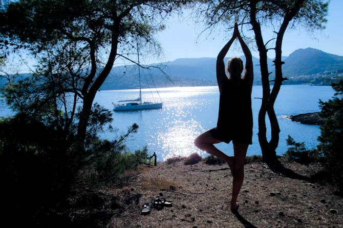 A profile of a person in a tree pose with the ocean as a backdrop