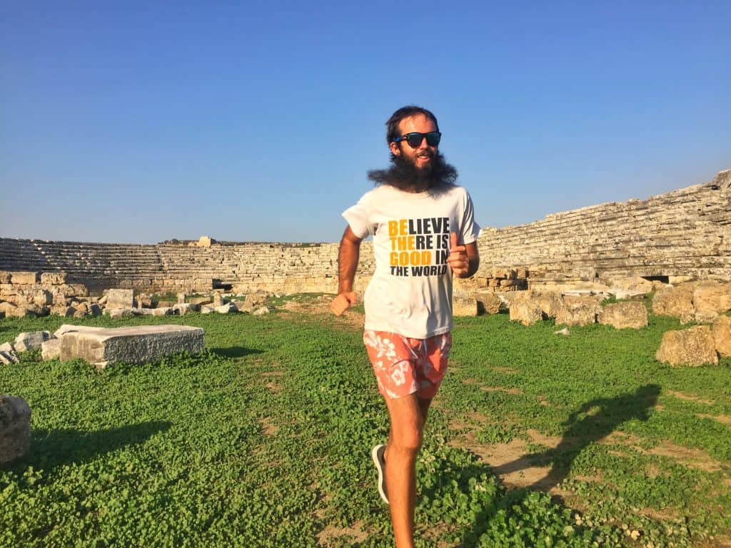 man with beard running at a Roman stadium