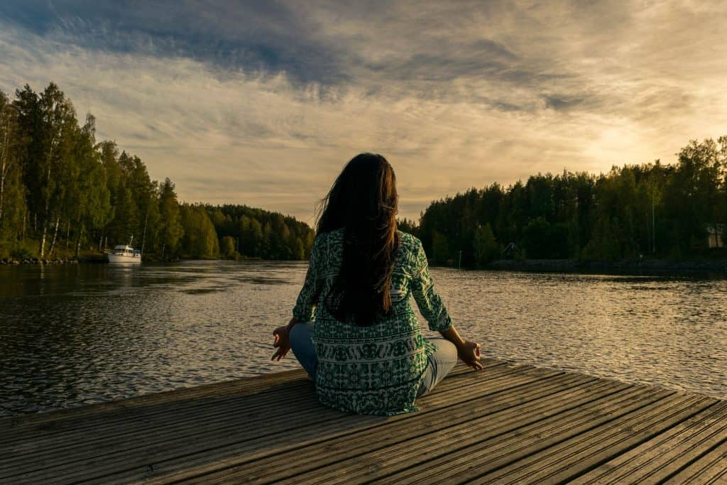 Girl meditating on a dock
