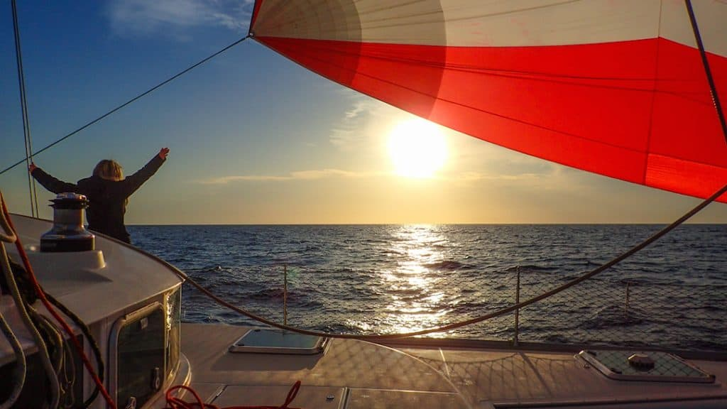 a red sail on a boat at sea