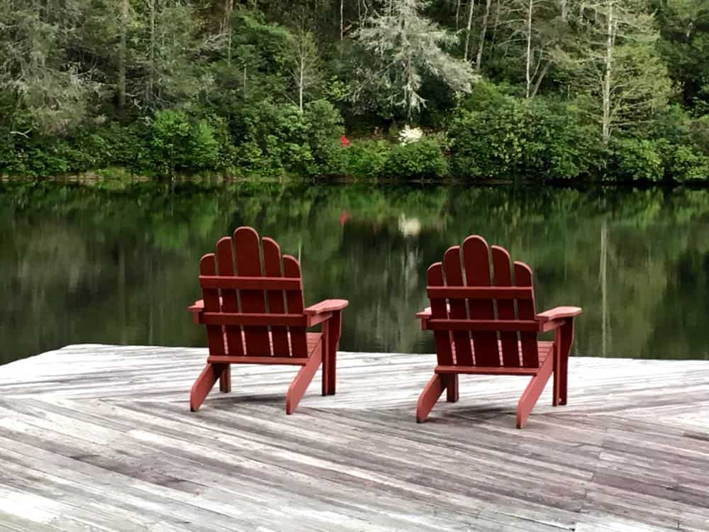 Two Adirondack chairs on a dock