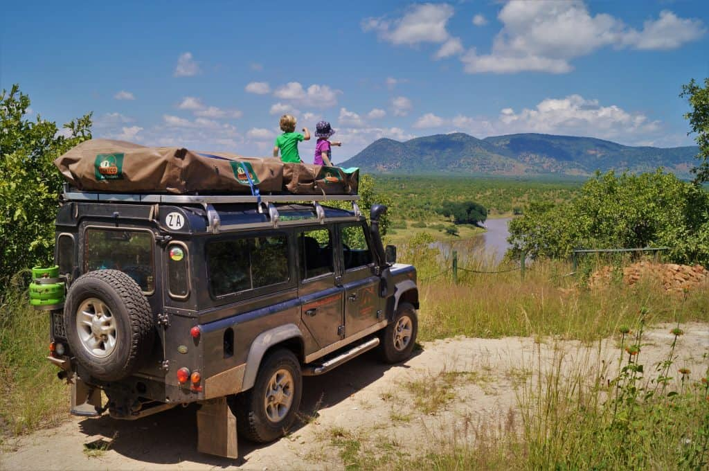 Two kids on top of a jeep on African Safari