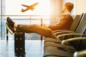 Travel safety tips: man at an airport resting his feet on luggage and looking out the window at a plane taking off