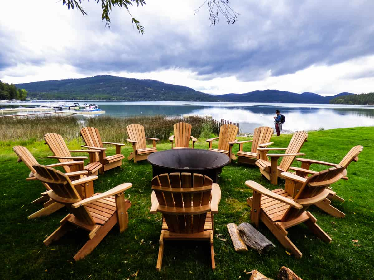 Wooden Adirondack chairs set in a circle around a firepit witht eh lake and mountains in the background