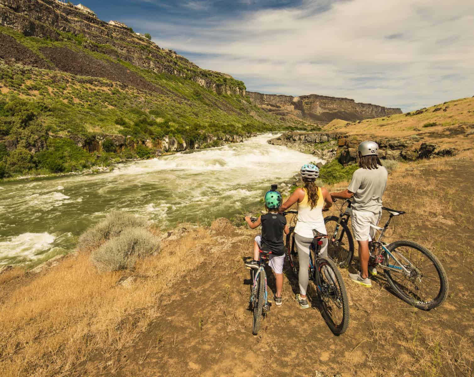 Idaho, Twin Falls. Young boy mountain biking near Snake River.