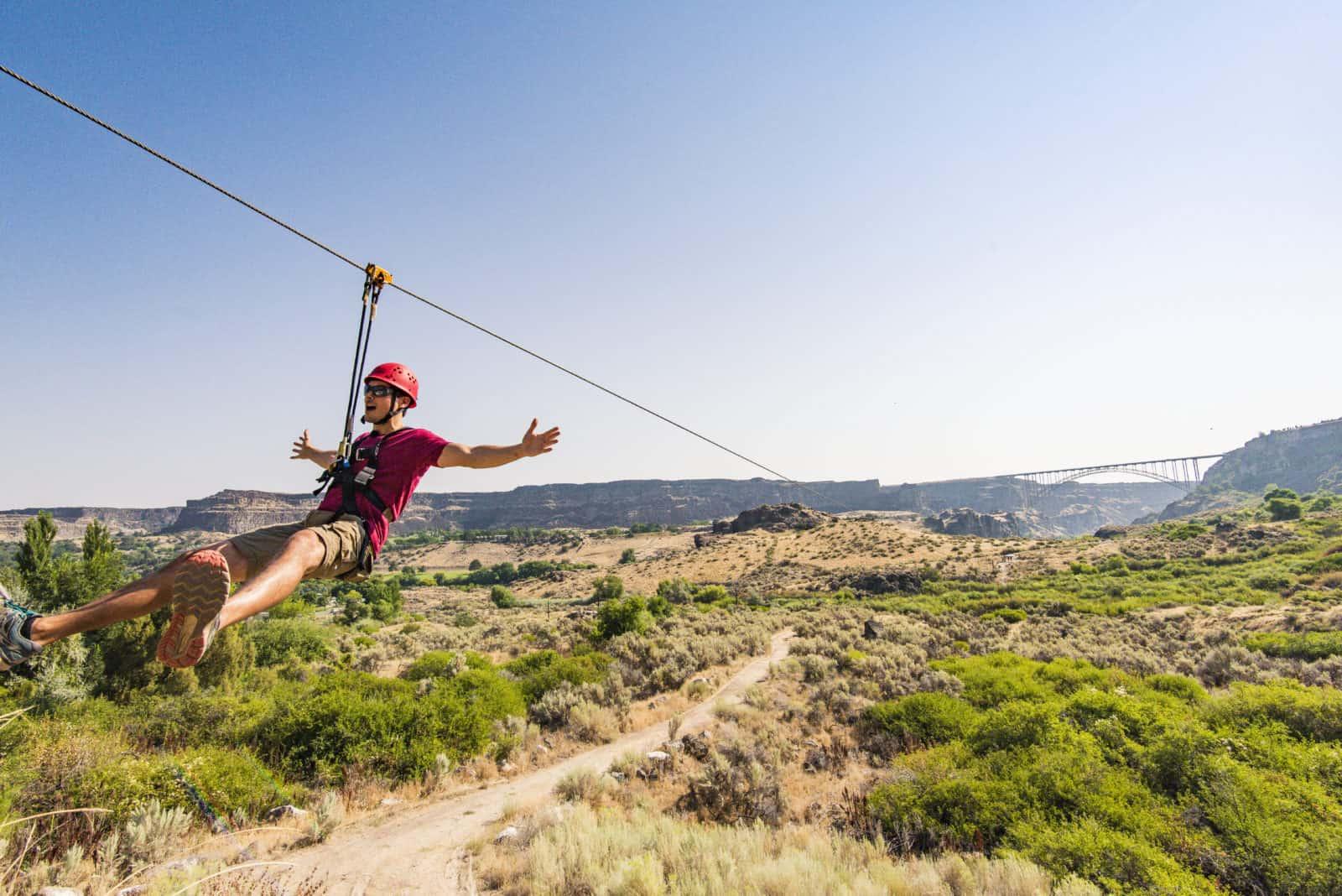 Man ziplining across a canyon