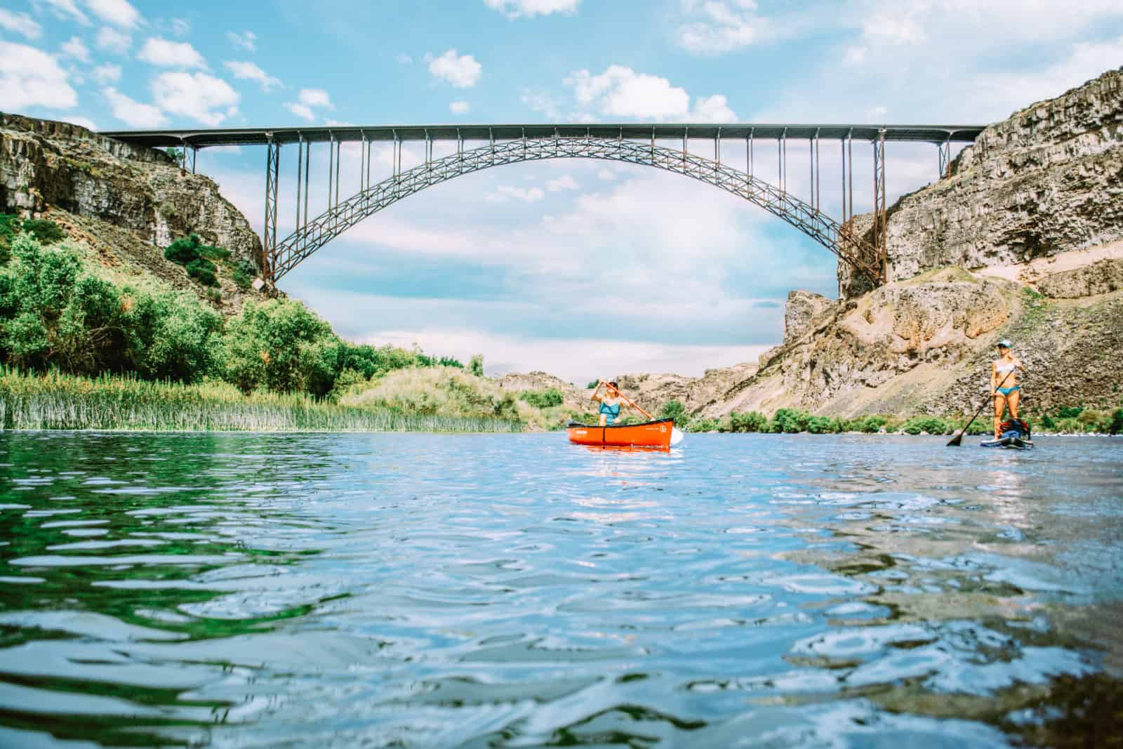 Orange canoe on water under a bridge