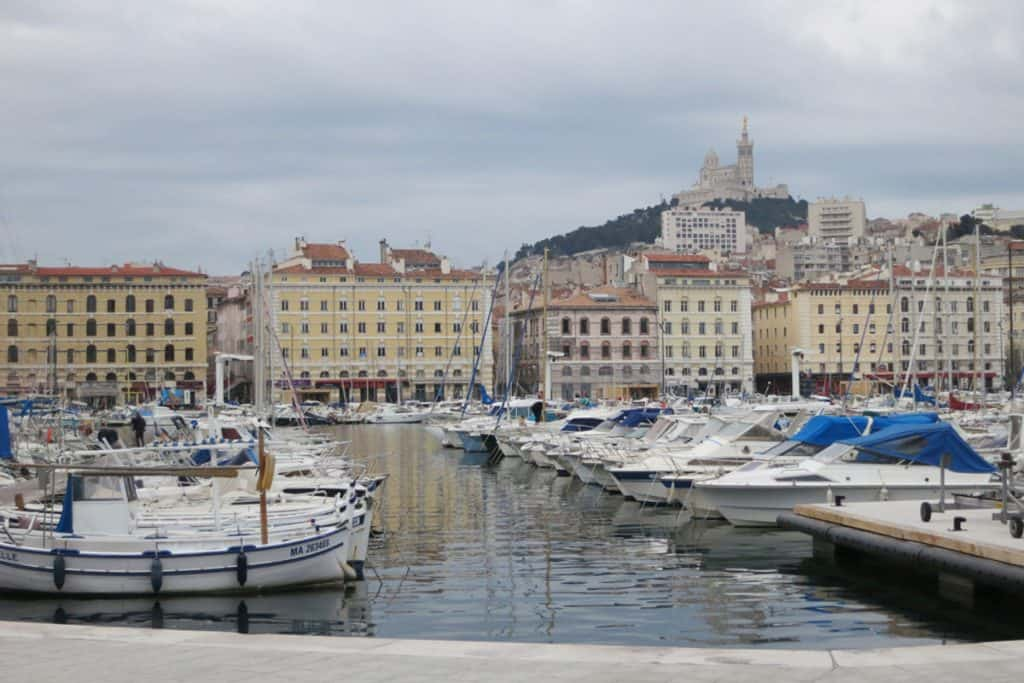 Harbour with boats in Marseille with buildings and hill in background
