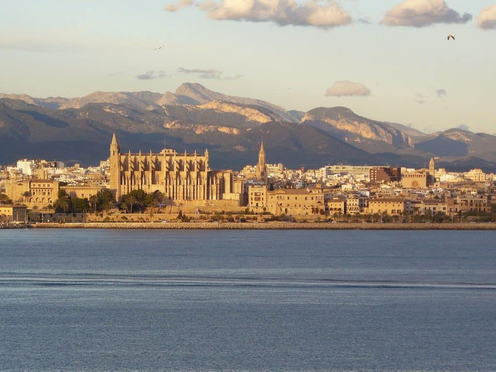 City skyline of Palma de Mallorca Spain with mountian in background and water in foreground