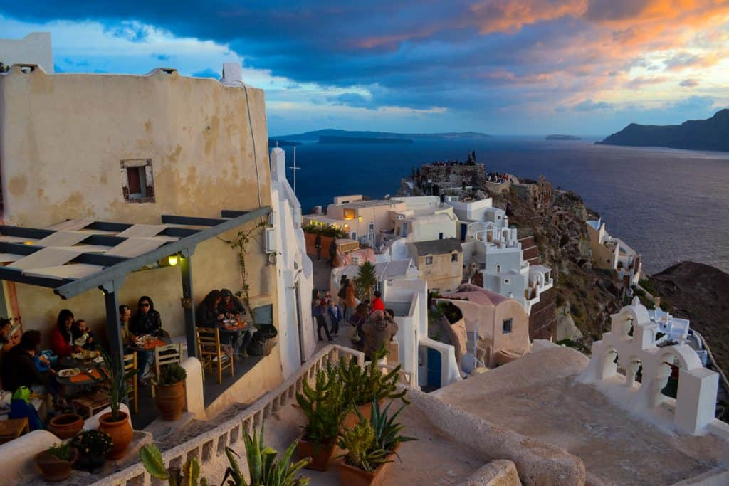 Street high on a cliff with white building overlooking the ocean in Santorini