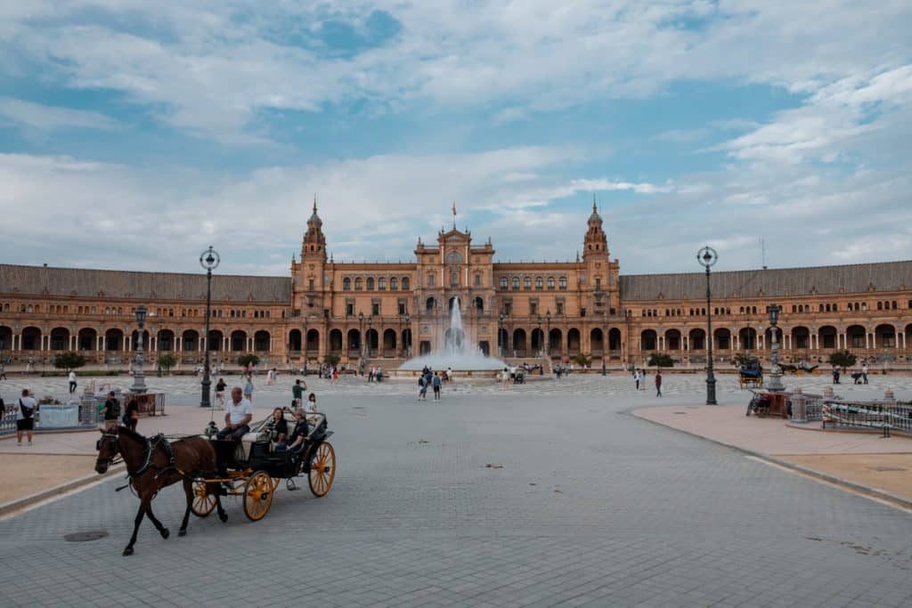 horse and buggy in front of a fountian and the buildings of Plaza de Espana