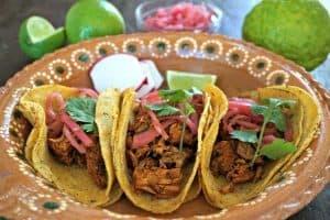 3 Cochinita Pibil tacos on a clay plate